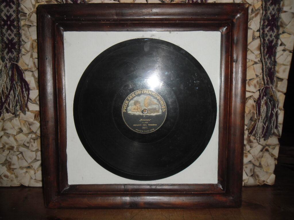 Граммофонная пластинка в раме под стеклом.