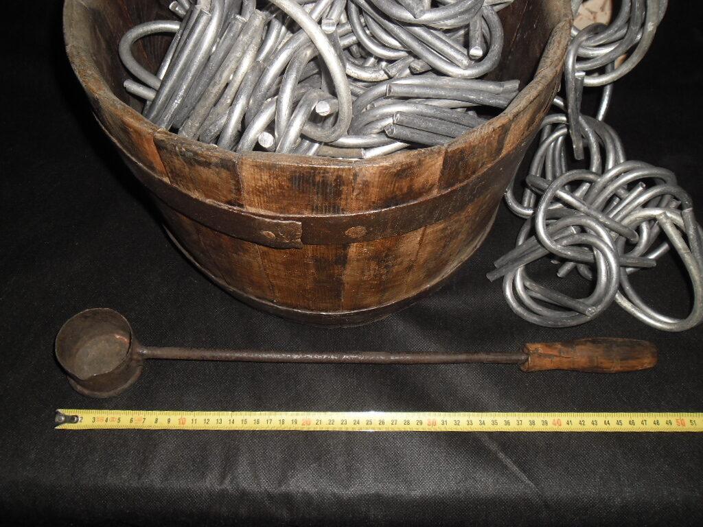 Олово в прутках в дубовой бочке с ковшиком для литья.