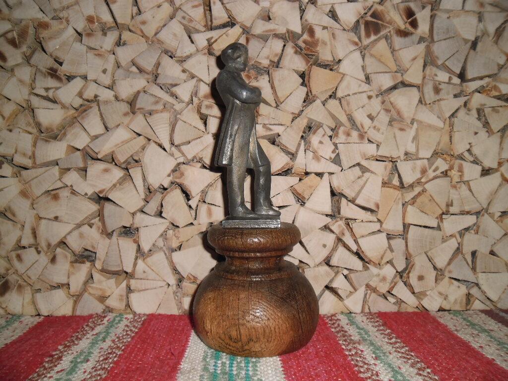 Metāla statuete uz ozolkoka paliktņa